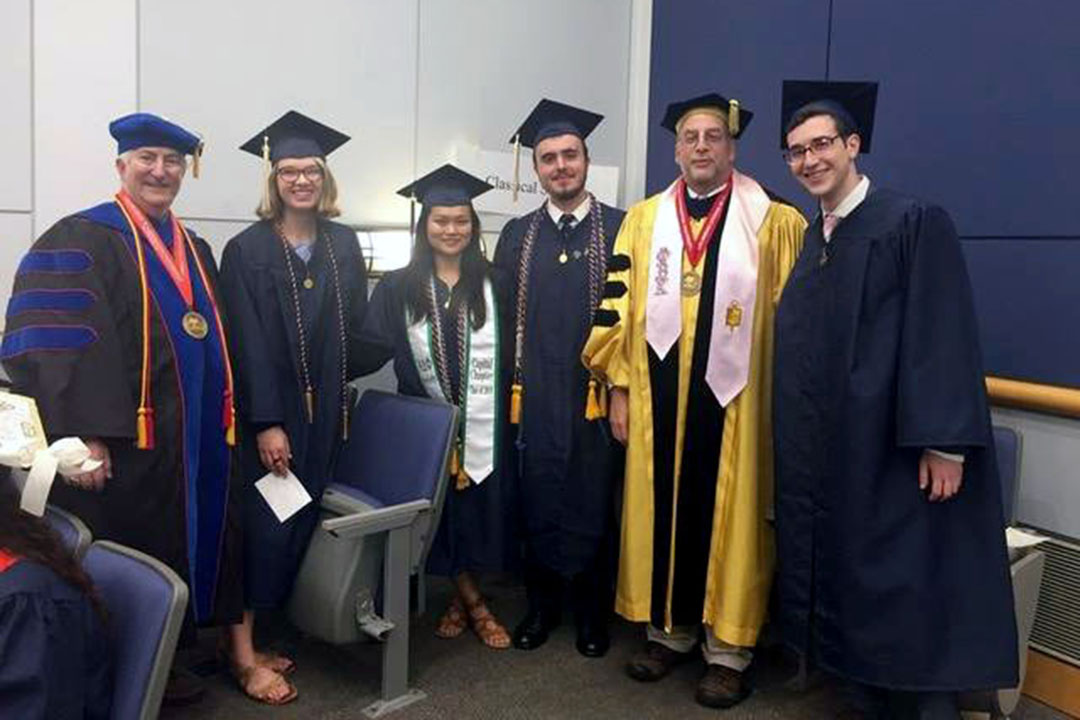A group of students and teachers in caps and gowns. From left, Prof. Eric Cline, Sydney Thatcher, Harper Hansen, William Berkery, Prof. Chris Rollston, and Jonah Bannett.