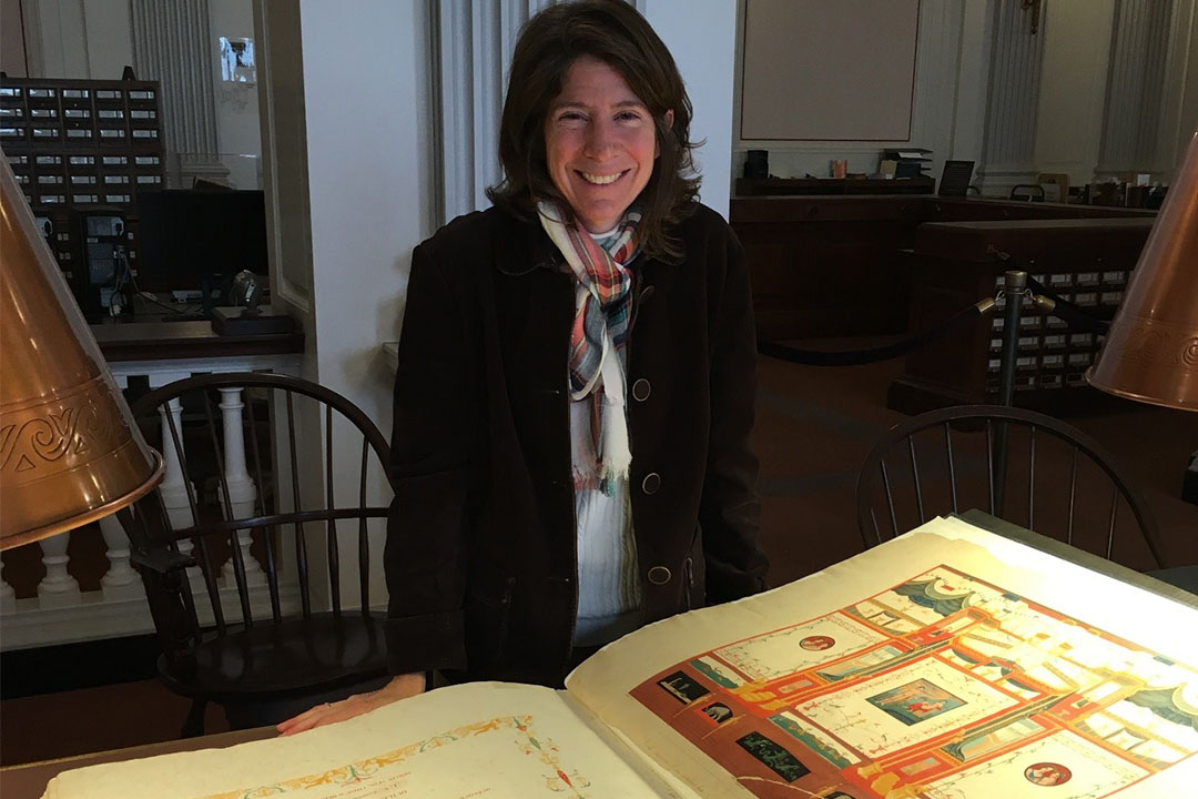 Elise Friedland standing in front of a huge, old book in the Library of Congress