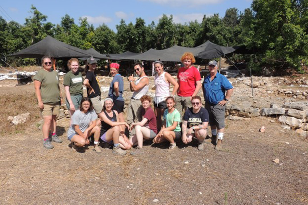 Eric Cline with a group of GW students standing outside tents at a dig site in Tel Kabri