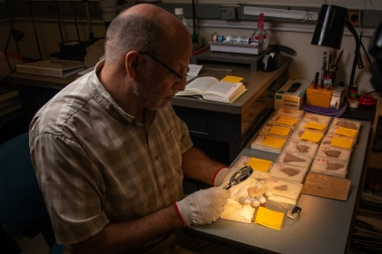 Chris Rollston examining small pottery fragments under a magnifying glass