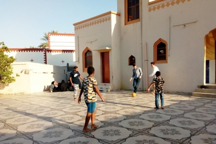 A group of children and GW students playing soccer outside on a terrace